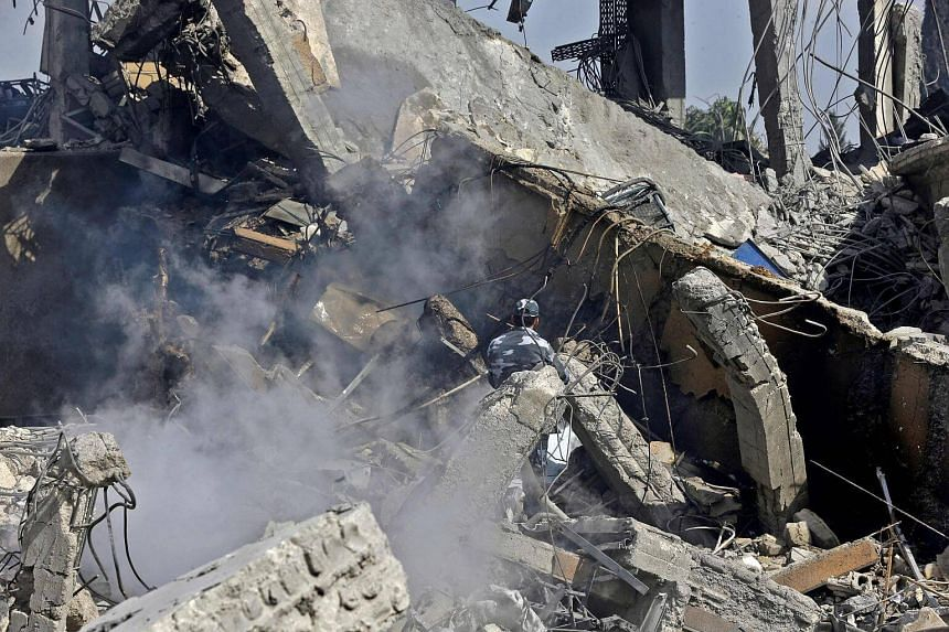 A Syrian soldier sprays water on the wreckage of a building described as part of the Scientific Studies and Research Centre compound in the Barzeh district, north of Damascus, on April 14, 2018.