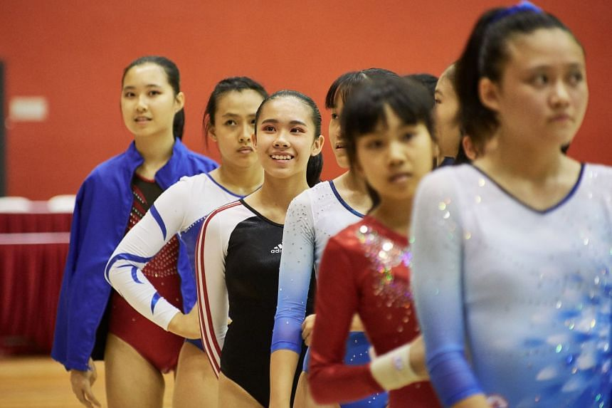 Marilene Low En Xing (3rd left) of CHIJ Secondary (Toa Payoh) smiling to supporters as she and other participants in the WAG Senior B Optional Girls Secondary Floor IAF category await the start.