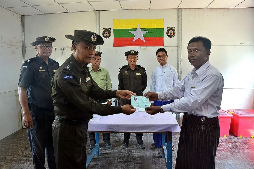 A Myanmar official handing over the identification document of a man from the repatriated Rohingya family.
