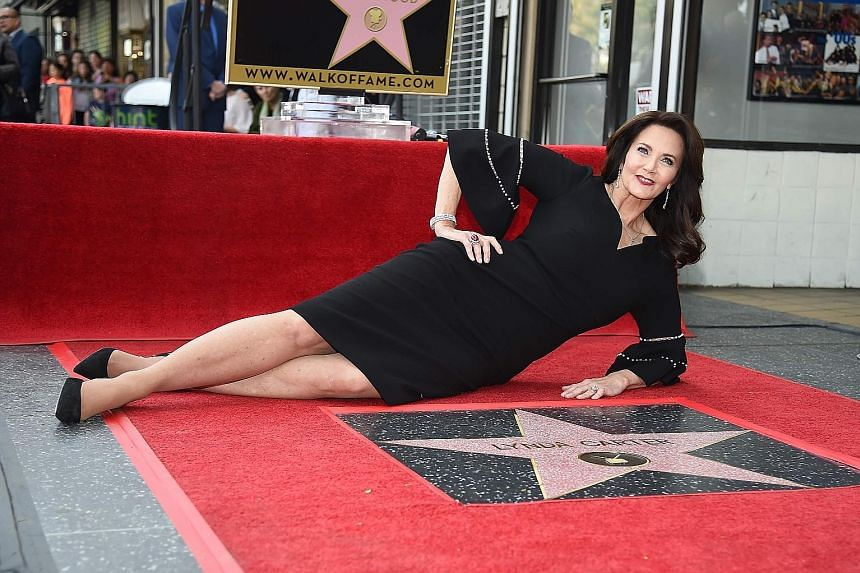 Actress Lynda Carter poses with her star on the Hollywood Walk of Fame.