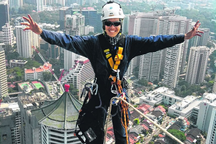 Mr Sky Lee, who was part of a rope-access team installing glass panels, at the top of Ion Orchard before it was completed. He says his weekly courses at SB Rope Access Specialist were full throughout last year. Workers inspecting a 90m-tall wind turb