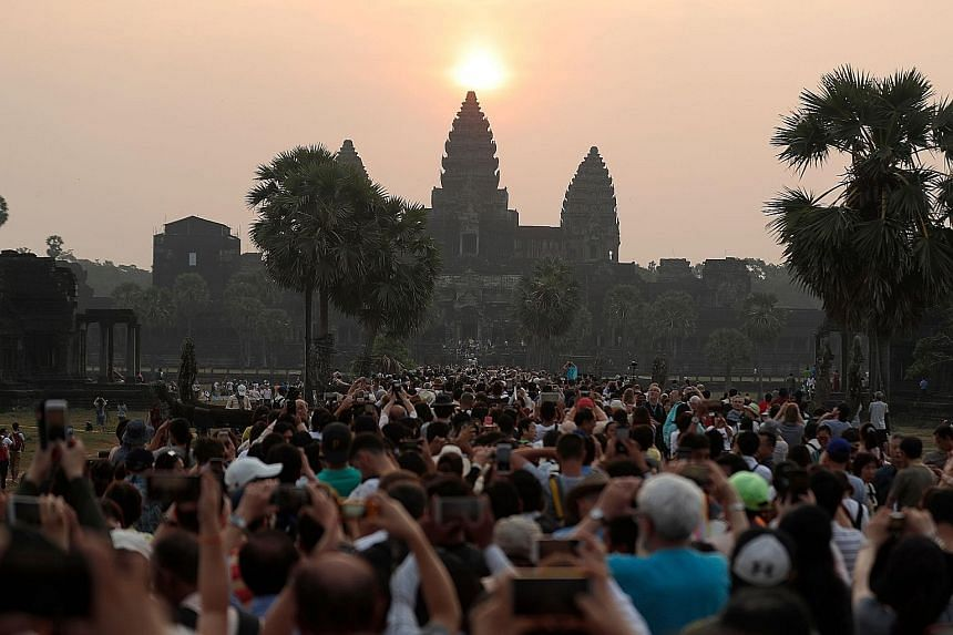 Huge crowds are drawn to the majestic sight of the sun rising over the central stupa of the famous Angkor Wat temple in Siem Reap, Cambodia, in this photo taken on March 22 this year. A rubbish collector clearing trash on the polluted Kuta beach near