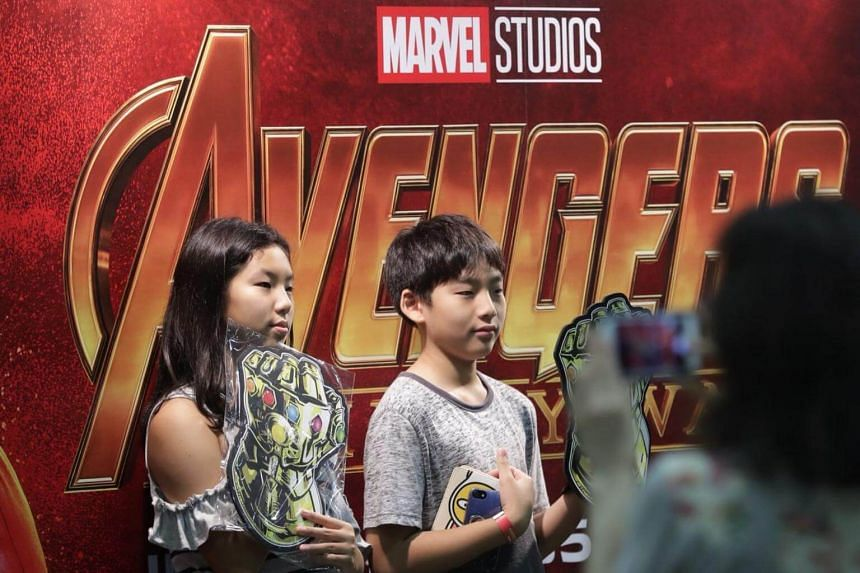 Children posing in front of an Avengers: Infinity War promotional board at Marina Bay Sands.