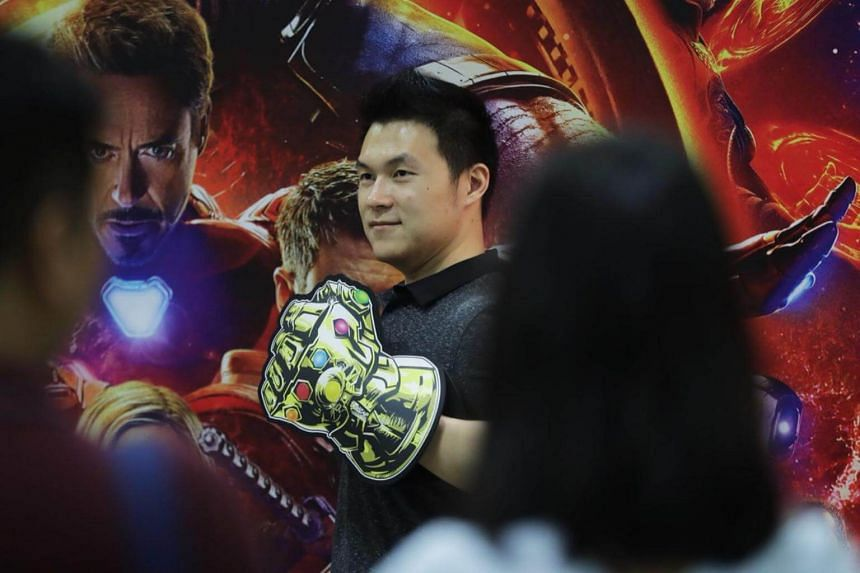 A male fan posing with an Avengers: Infinity War promotional board and a replica of the Infinity Gauntlet from the film.
