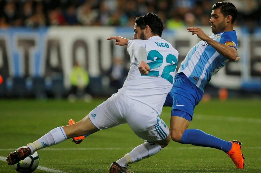 Real Madrid's Isco in action with Malaga's Miguel Torres in La Rosaleda, Malaga, Spain on April 15, 2018.