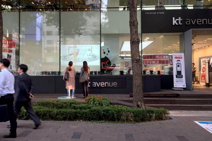 People walking past telco KT Corp's shop in the posh Gangnam district, in South Korea.