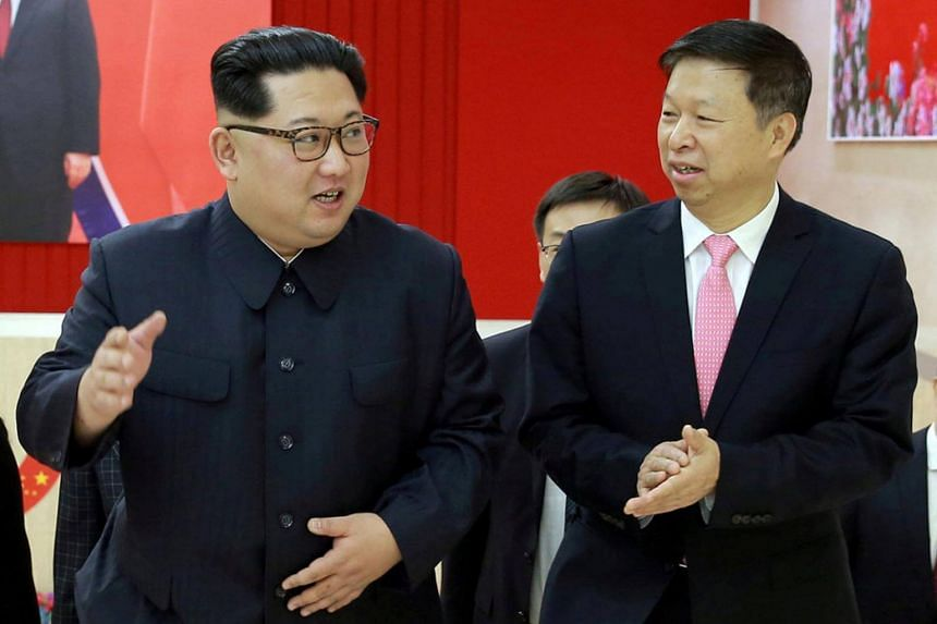 North Korean leader Kim Jong Un (left) speaking to Song Tao, the head of the China Communist Party's International Department.