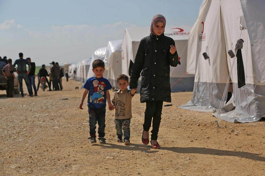 Syrian children walk in a camp for displaced Syrians from the former rebel bastion of Douma, in al-Bil, Syria on April 13, 2018.