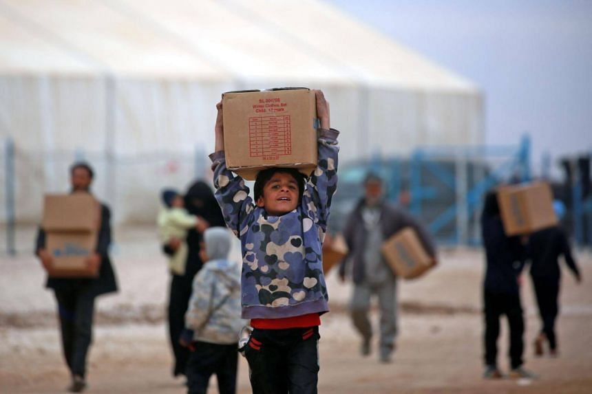 Displaced Syrians carry boxes of humanitarian aid supplied by United Nations Children's Fund at a refugee camp in Syria's Hassakeh province on Feb 26, 2018.