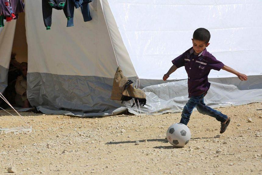 A Syrian boy kicks a ball in a camp for displaced Syrians in al-Bil, Syria on April 13, 2018.