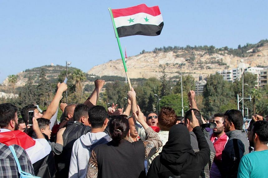 Syrians waving a national flag during a gathering to show support for the Syrian government at Umayyad square in Damascus, Syria, on April 14, 2018.