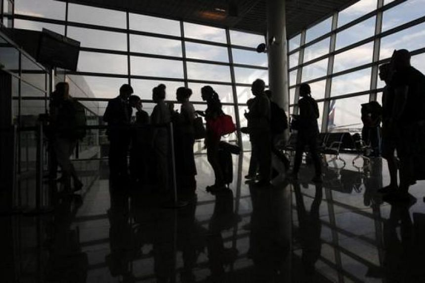 People line up before boarding an Aeroflot plane heading to the Cuban capital Havana at Moscow's Sheremetyevo airport on July 6, 2013.
