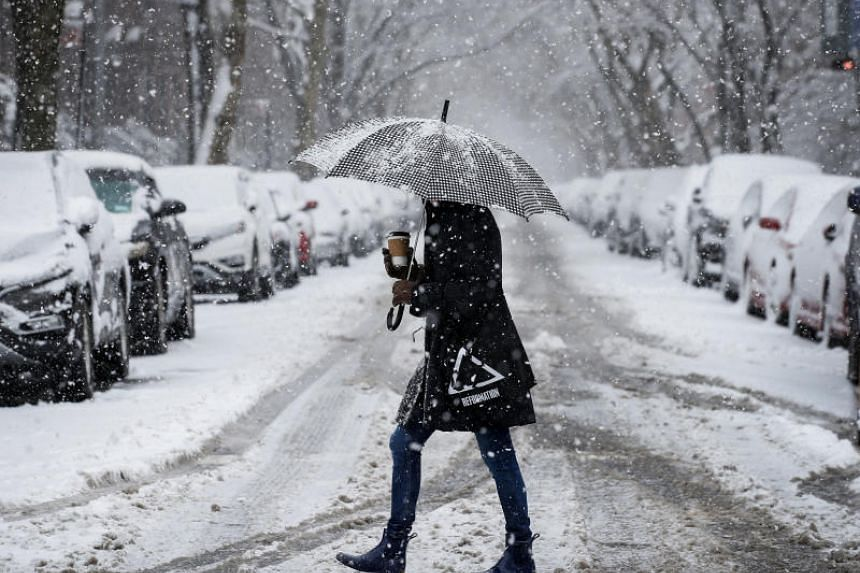 A woman walks in the snow during a winter nor'easter storm in the Brooklyn borough of New York, US on March 21, 2018.