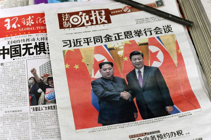 The front pages of Chinese evening newspapers show images of Chinese President Xi Jinping with North Korean leader Kim Jong Un are displayed at a newspaper stand in Beijing on March 28, 2018.
