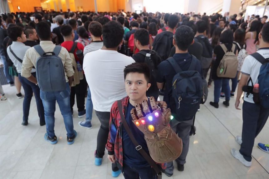 Iron Man fan Jason Foo posing with a replica of the Infinity Gauntlet.
