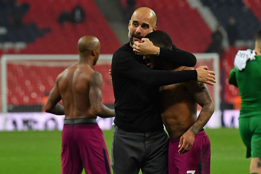 Manchester City's Spanish manager Pep Guardiola embraces Manchester City's English midfielder Raheem Sterling on the pitch after the English Premier League football match between Tottenham Hotspur and Manchester City.