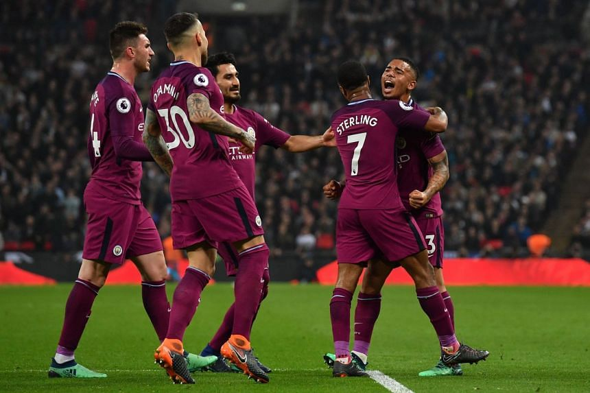 Manchester City's English midfielder Raheem Sterling (second, right) celebrates with Manchester City's Brazilian striker Gabriel Jesus (right) and teammates after scoring their third goal during the English Premier League football match between Totte