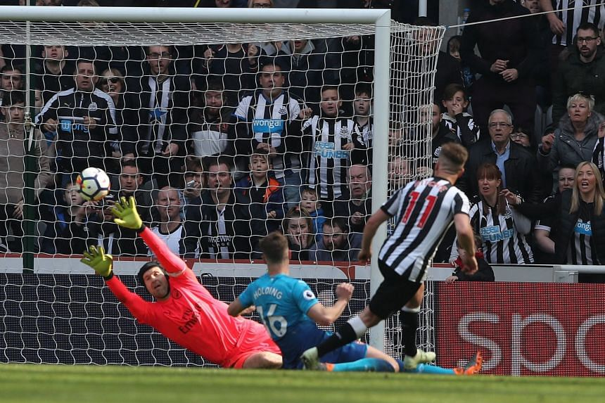 Newcastle's Matt Ritchie firing the winning goal past Arsenal goalkeeper Petr Cech at St James' Park yesterday with the three points keeping the Magpies virtually safe, while Arsene Wenger comes under further heat.