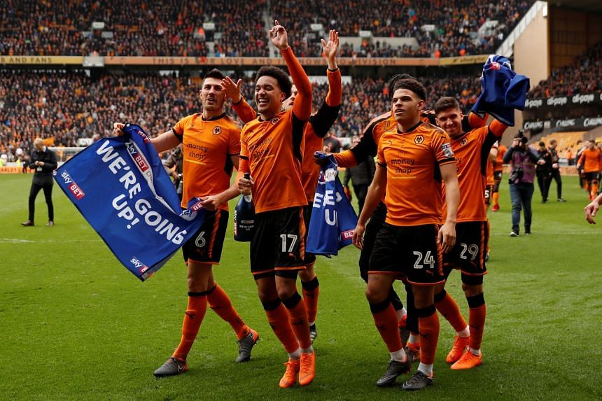 Wolverhampton Wanderers players celebrate promotion to the Premier League after their 2-0 win over Birmingham City yesterday.