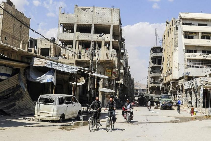 Syrian citizens cycle next to a damaged building in Douma, Syria, on April 15, 2018.