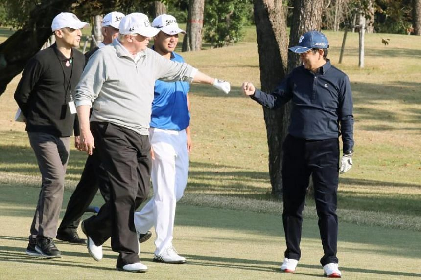 US President Donald Trump (centre) gestures to Japanese Prime Minister Shinzo Abe (right) while playing golf with Japanese professional golfer Hideki Matsuyama (second right) at the Kasumigaseki Country Club Golf Course in Kawagoe, Japan on Nov 5, 20