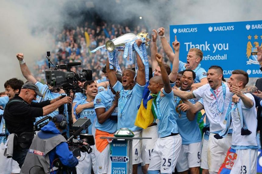 Manchester City's Vincent Kompany (centre) lifts the Premier League trophy after their victory during the English Premier League football match between Manchester City and West Ham United at the Etihad Stadium in Manchester on May 11, 2014.