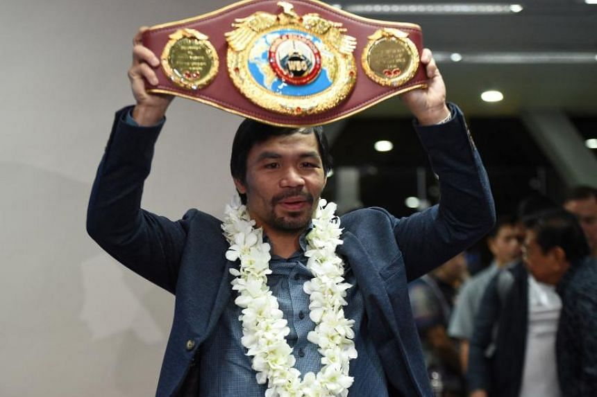 Manny Pacquiao holding his welterweight title belt after defeating Jessie Vargas at Manila airport on Feb 26, 2017.