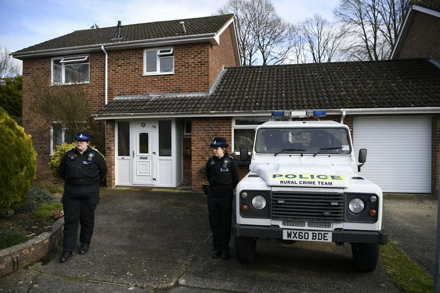 Police standing outside a house that is thought to be the home of Sergei Skripal in Salisbury, Britain.