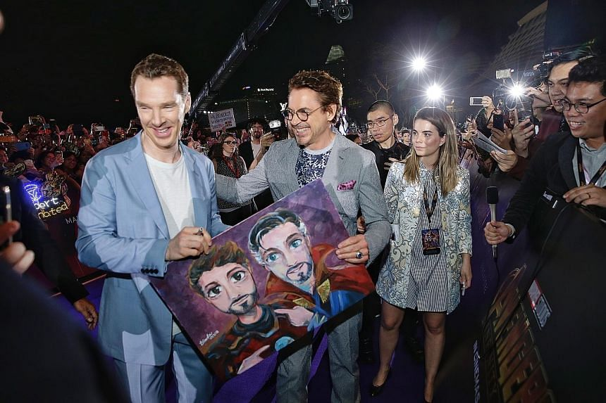 Actor Benedict Cumberbatch (far left), who plays Doctor Strange in the upcoming film Avengers: Infinity War, and Robert Downey Jr, who plays Iron Man, with a drawing of their characters by a fan, at the movie's red-carpet fan event at the Marina Bay