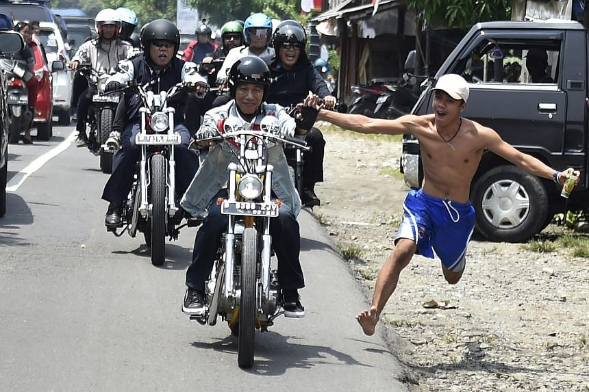 An enthusiastic Indonesian running to connect with President Joko Widodo, in a show of support for the country's top leader. Mr Joko and his entourage were on a 30km motorbike tour of the rural areas of Sukabumi in West Java last week.
