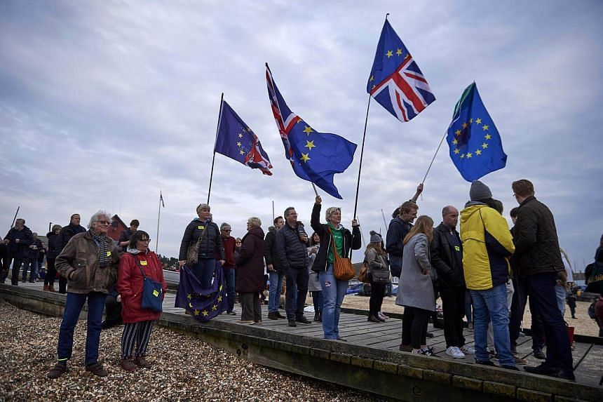 Pro-EU supporters look on during a demonstration in Whitstable, south-east England, on April 8, 2018.