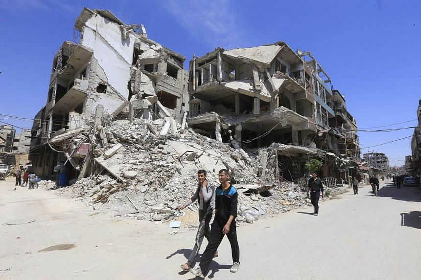 People are seen walking in Douma on the outskirts of Damascus, on April 16, 2018.