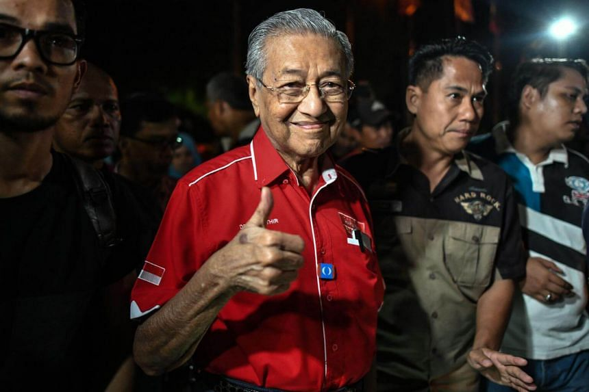 Former Malaysian PM Mahathir Mohamad gestures as he arrives for a rally ahead of the 14th general election on Malaysia's island of Langkawi, on April 15, 2018.