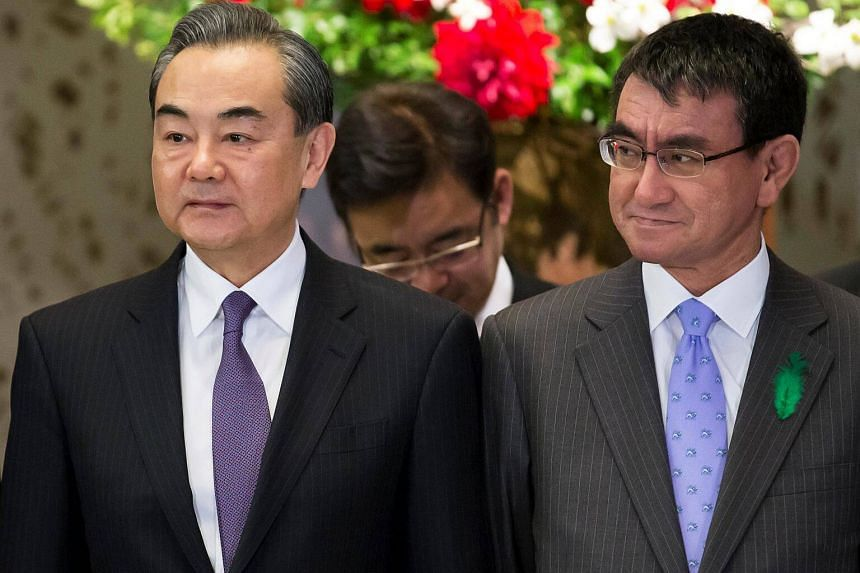China's foreign minister Wang Yi (left) and Japan's foreign minister Taro Kono pose during a photo session ahead of a high-level Japan-China economic dialogue in Tokyo, on April 16, 2018.