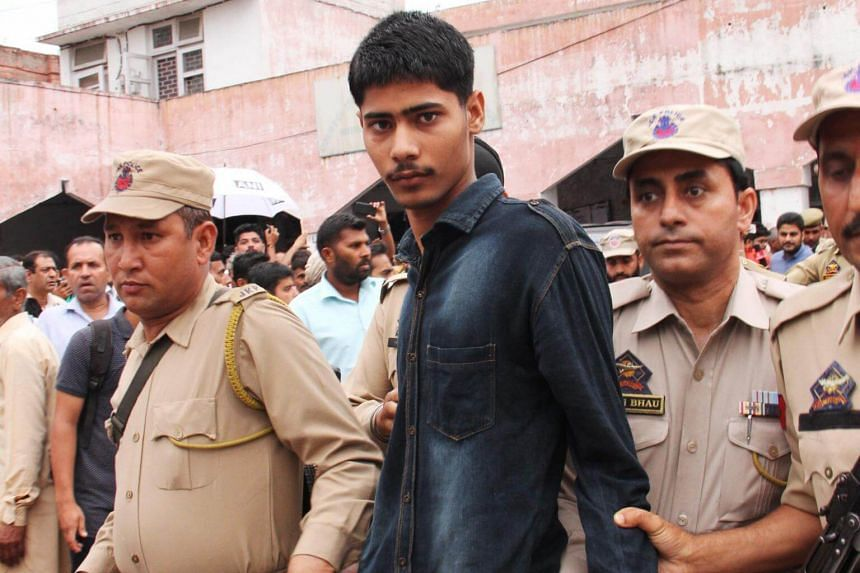 Policemen escorting one of the accused in the gang rape and killing of an eight-year-old girl at the District and Sessions court in Kathua.