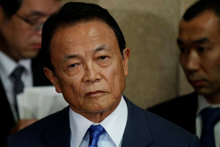 Japan's Finance Minister Taro Aso (centre) speaking to reporters after a Cabinet meeting, on March 13, 2018.