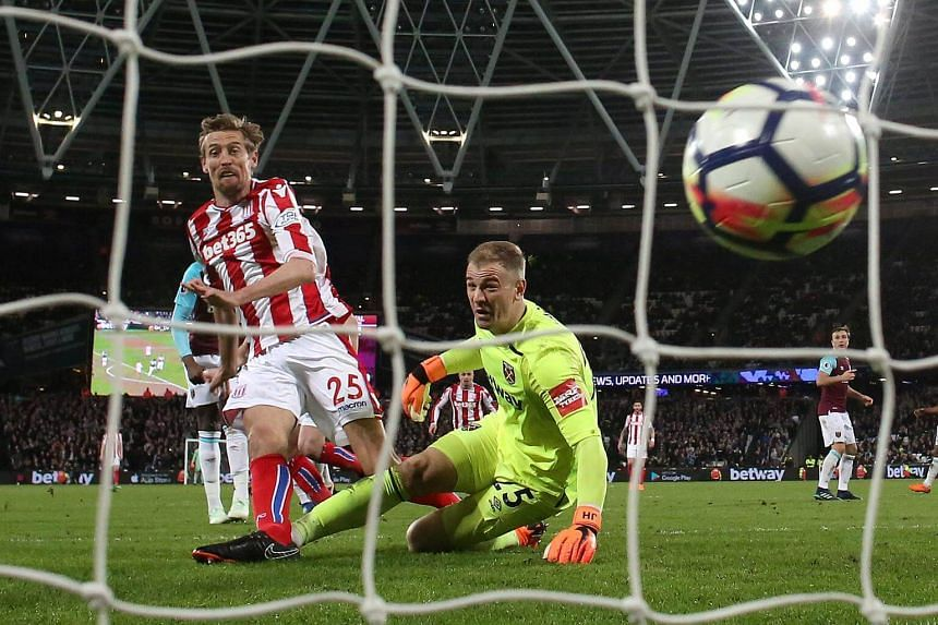 Stoke City's Peter Crouch scores their first goal as West Ham United's Joe Hart looks on in London Stadium, London, Britain on April 16, 2018.