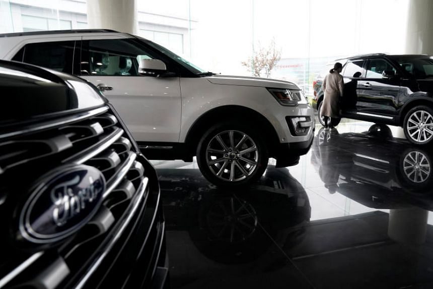 A woman looks at Ford cars at a dealer shop in Shanghai, China, on April 5, 2018.