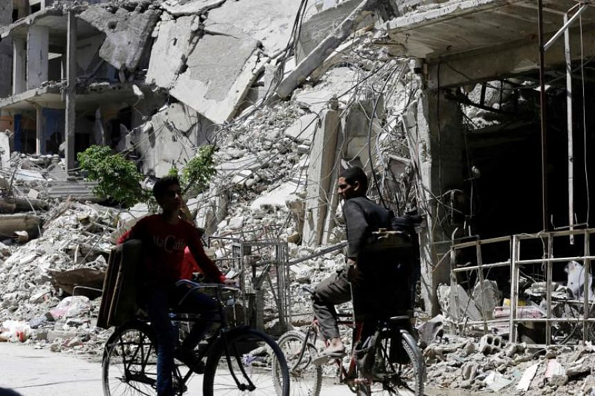 Syrians cycle along a damaged street in Douma on the outskirts of Damascus on April 16, 2018.