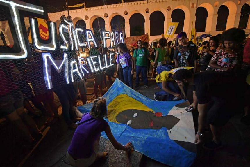 People gather in Lapa neighbourhood, Rio de Janeiro, Brazil during a demonstration marking one month of activist Marielle Franco's murder on April 14, 2018.