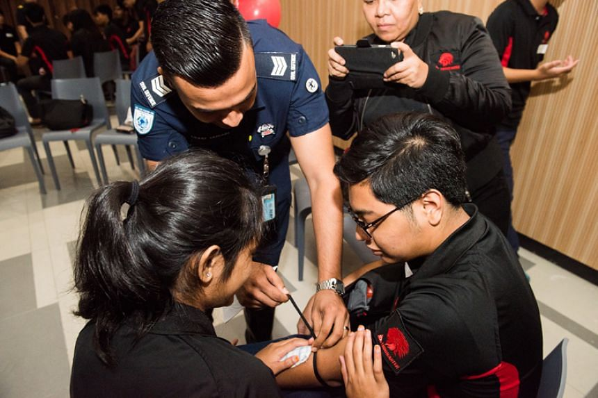 """Participants at the seventh annual Singapore Civil Defence Force Civil Defence Lionhearters Forum entered the Singapore Book of Records for the largest demonstration of """"Bleeding Control in First Aid""""."""