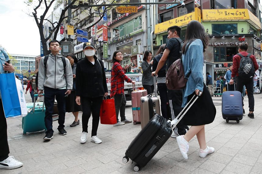 Chinese tourists walk along Myeongdong Street in Seoul on April 13, 2018.