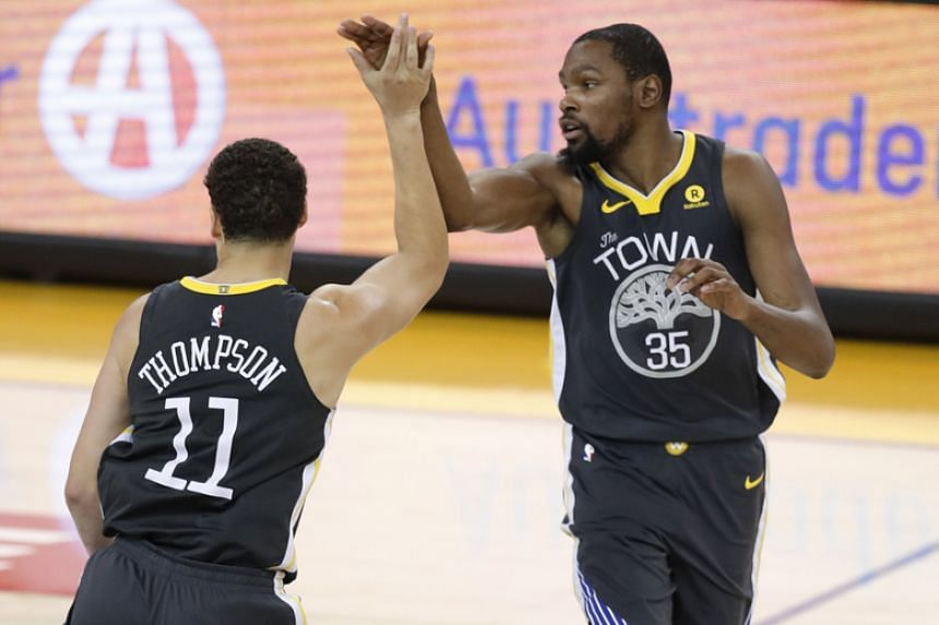 Golden State Warriors' Klay Thompson and Kevin Durant gesture during the National Basketball Association game against the San Antonio Spurs at the Oracle Arena in Oakland, California, on April 16, 2018.