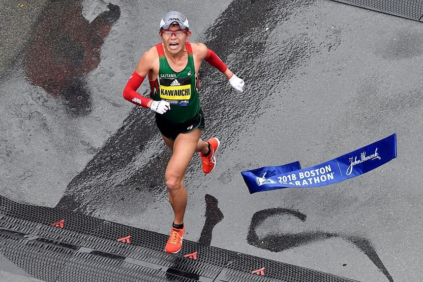 Amateur runner Yuki Kawauchi, 31, crosses the finish line to become the first Japanese man in 31 years to win the Boston Marathon on Monday. He has run four marathons this year and won all of them.