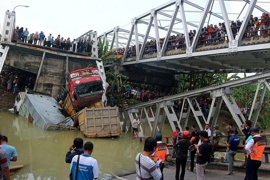 A crowd of onlookers gathered at the scene after a bridge connecting Lamongan and Tuban in Indonesia's East Java province collapsed and fell into the Bengawan Solo River yesterday. Three trucks and a motorcycle plunged into the water, and two truck d