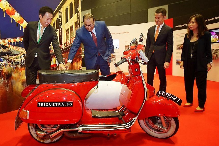 Minister for Trade and Industry (Industry) S. Iswaran looking at a vintage Vespa with a sidecar at the marketing and technology showcase at the Tourism Industry Conference 2018. With him are (from left) STB chairman Chaly Mah, chief executive Lionel