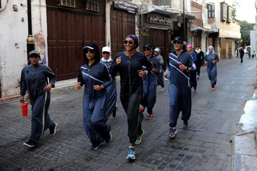Saudi women jog in the streets of Jeddah's historic al-Balad district on March 8, 2018.