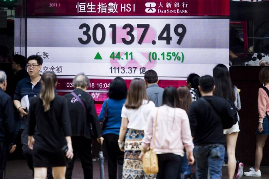 Pedestrians walk past an electronic sign displaying the closing stock numbers for the Hang Seng Index in Hong Kong on April 3, 2018.