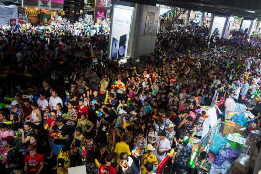 Thousands of revellers carrying toy water guns occupy Silom Road in central Bangkok during a mass water fight as they celebrate Songkran on April 14, 2018.