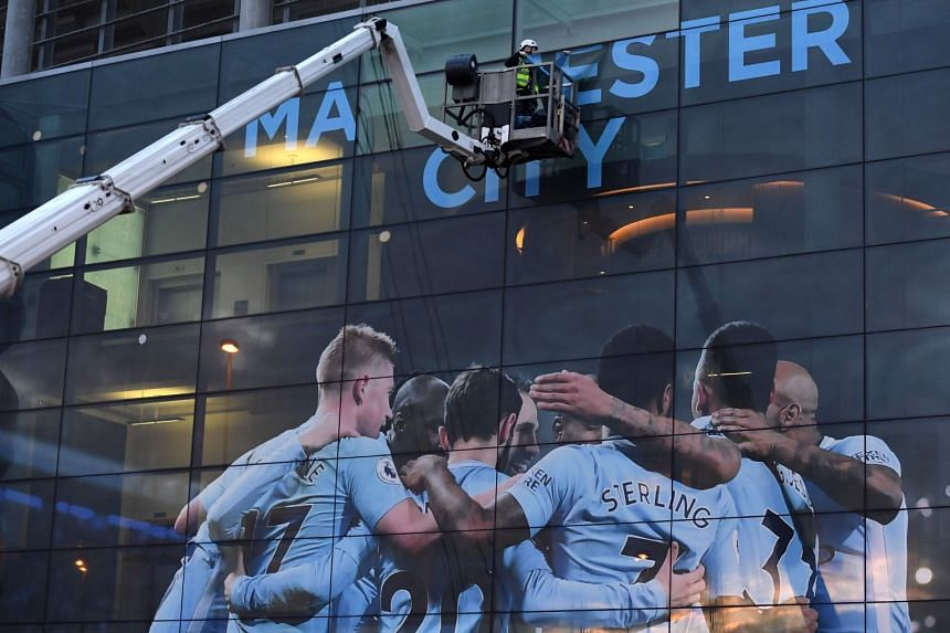 A workman changing the awning at City's Etihad Stadium on April 15, 2018, to mark their Premier League title win.